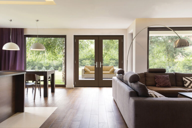 ThermaTru Patio Doors Classically elegant living room with sofa, a metal standing lamp open to the dining room